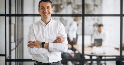 homme souriant devant une verrière entreprise